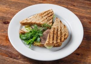 Сэндвич с печеной говядиной, зеленым салатом, маринованным огурчиком и томатным соусом